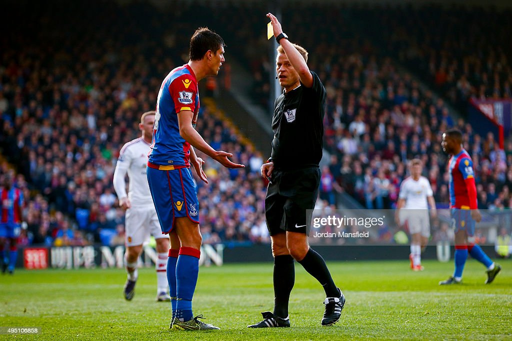Referee Mike Jones shows Martin Kelly of Crystal Palace a yellow card during the Barclays Premier League match between Crystal Palace and Manchester United at Selhurst Park on October 31, 2015 in London, England.
