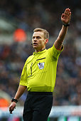 Referee Mike Jones signals during the Barclays Premier League match between Newcastle United and Arsenal at St James' Park on March 21 2015 in...