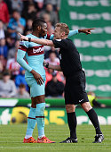 Referee Mike Jones talks with Emmanuel Emenike of West Ham United during the Barclays Premier League match between Stoke City and West Ham United at...