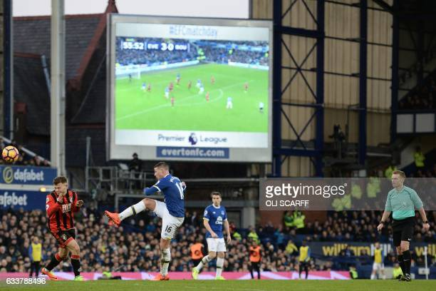 Referee Mike Jones watches as Everton's Scottishborn Irish midfielder James McCarthy has an unsuccessful shot in front of the big screen during the...