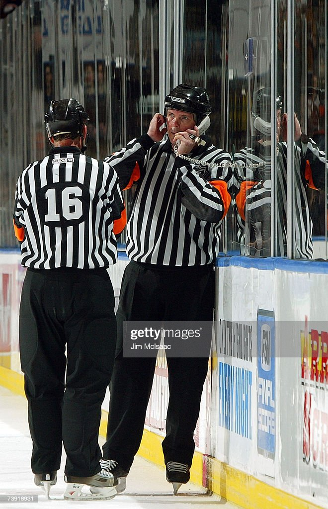 Referee Mike Leggo (R) talks on the phone in the review of his call late in the third period of Game 4 of the 2007 Eastern Conference Quarterfinals between the New Yorl Islanders and the Buffalo Sabres on April 18, 2007 at Nassau Coliseum in Uniondale, New York. The Sabres won the game 4-2 and lead the series 3-1.