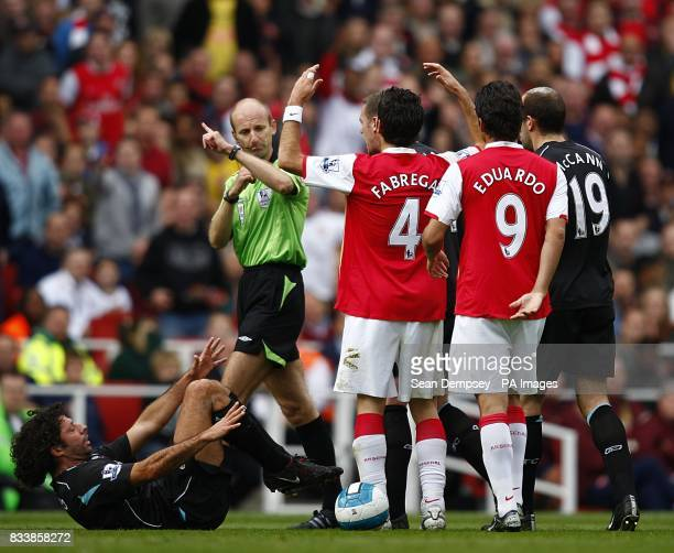 Referee Mike Riley has a word with Arsenal's Francesc Fabregas after fouling Bolton Wanderers' Ivan Campo