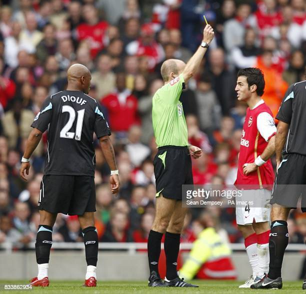 Referee Mike Riley shows Arsenal's Francesc Fabregas a yellow card as Bolton Wanderers' ElHadji Diouf looks on both were booked for dissent
