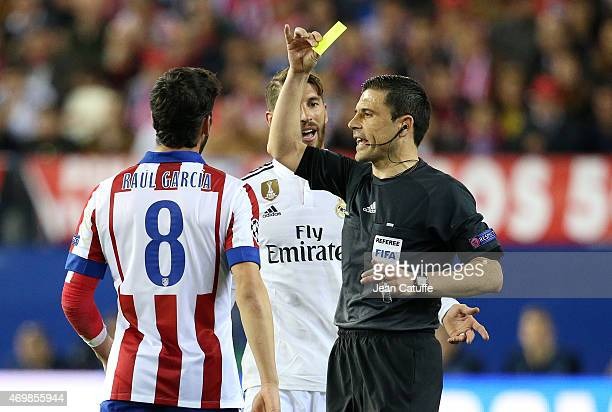 Referee Milorad Mazic delivers a yellow card to both Raul Garcia Escudero of Atletico Madrid and Sergio Ramos of Real Madrid during the UEFA...