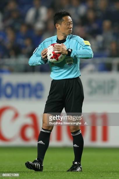Referee Minoru Tojo checks air pressure of the matchball prior to replacing it during the JLeague J1 match between Gamba Osaka and Sanfrecce...