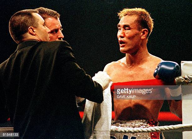 Referee Mitch Halpern and another unidentified ringside official look at the cuts on the face of WBA world superfeatherweight defending champion...