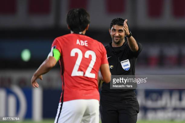 Referee Mohammed Abdulla Hassan speaks to Yuki Abe of Urawa Red Diamonds during the AFC Champions League quarter final first leg match between...