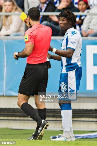 Referee Mohammed AlHakim hand out yellow card to Sam Adekugbe of IFK Goteborg during the Allsvenskan match between IFK Goteborg and BK Hacken at...