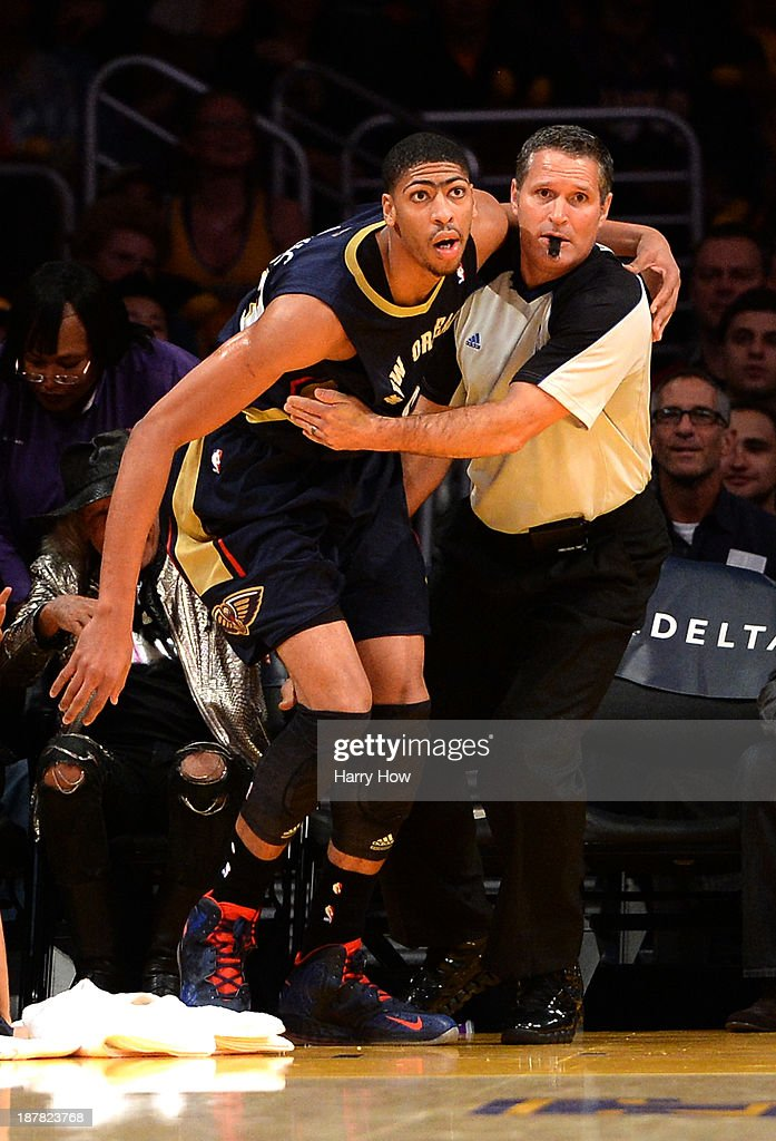 Referee Monty McCutchen #13 helps up Anthony Davis #23 of the New Orleans Pelicans during a 116-95 loss to the Los Angeles Lakers at Staples Center on November 12, 2013 in Los Angeles, California.