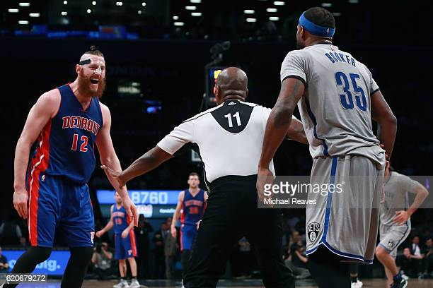 Referee Monty McCutchen holds back Aron Baynes of the Detroit Pistons and Trevor Booker of the Brooklyn Nets during a dispute during the second half...