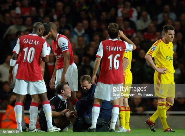 Referee Mr M Clattenburg is surrounded by Arsenal players as he receives treatment for an injury