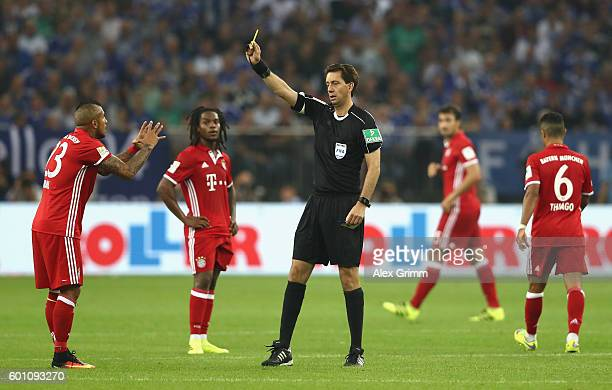 Referee Muenchen a yellow card during the Bundesliga match between FC Schalke 04 and Bayern Muenchen at VeltinsArena on September 9 2016 in...