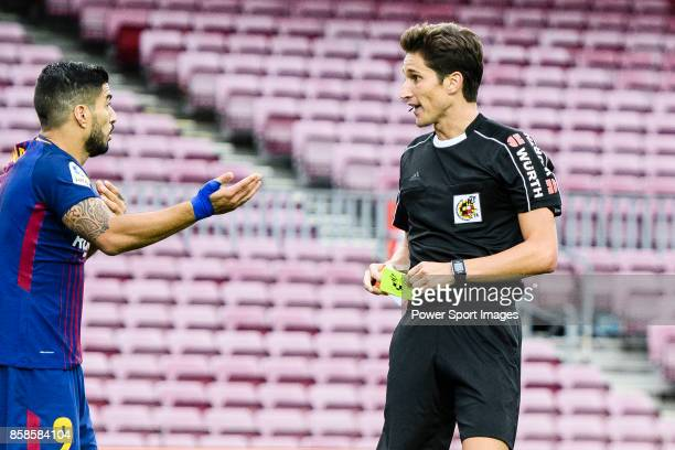 Referee Munuera Montero issues yellow card to Luis Alberto Suarez Diaz of FC Barcelona during the La Liga 201718 match between FC Barcelona and Las...