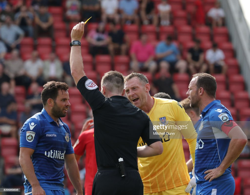Referee Neil Hair shows a yellow card to Sam Wood of Eastleigh during the National League match between Leyton Orient and Eastleigh at The Matchroom Stadium on August 26, 2017 in London, United Kingdom.