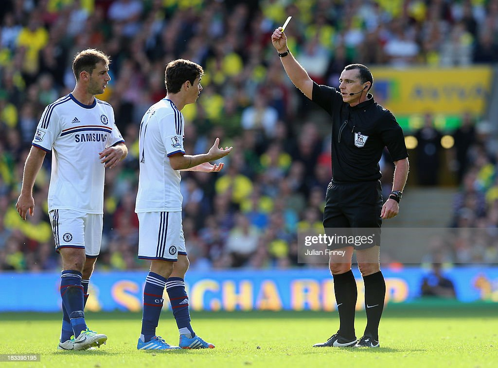 Referee Neil Swarbrick shows Oscar of Chelsea a yellow card during the Barclays Premier League match between Norwich City and Chelsea at Carrow Road on October 6, 2013 in Norwich, England.