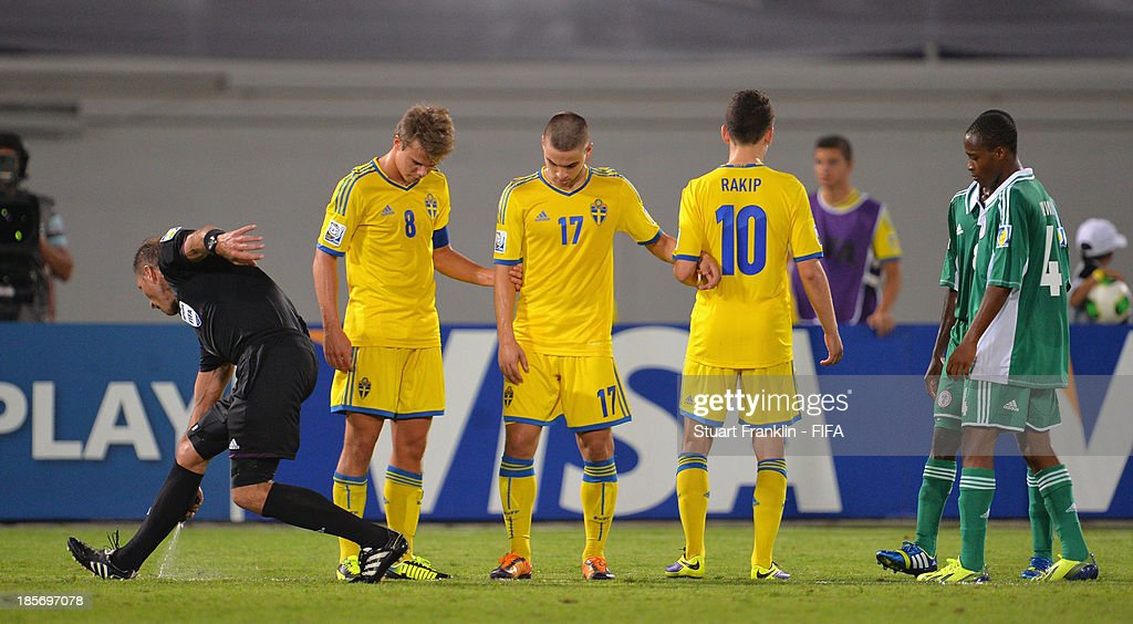 Referee Nestor Pitana marks a free kick line with disappearing foam during the FIFA U17 group F match between Sweden and Nigeria at Khalifa Bin Zayed Stadium on October 22, 2013 in Al Ain, United Arab Emirates.