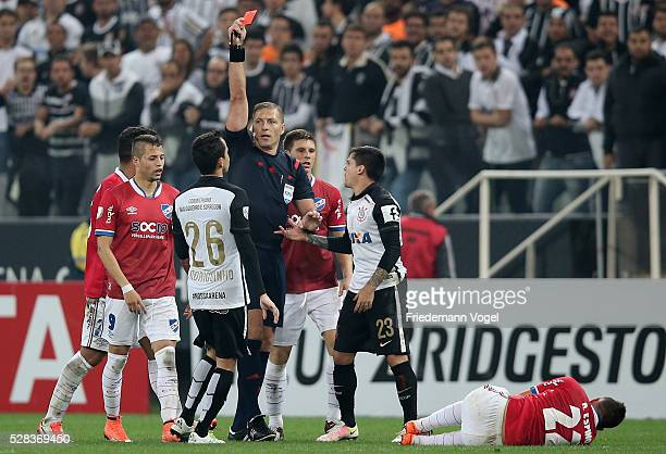 Referee Nestor Pitana shows the red card to Rodriguinho of Corinthians during a match between Corinthians and Nacional URU as part of round of 16 of...