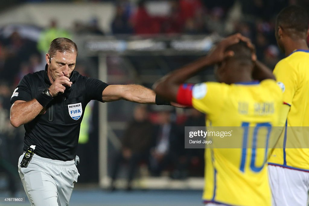Referee Nestor Pitana signals a penalty kick as Walter Ayovi and <a gi-track='captionPersonalityLinkClicked' href=/galleries/search?phrase=Frickson+Erazo&family=editorial&specificpeople=7817907 ng-click='$event.stopPropagation()'>Frickson Erazo</a> of Ecuador react during the 2015 Copa America Chile Group A match between Chile and Ecuador at Nacional Stadium on June 11, 2015 in Santiago, Chile.
