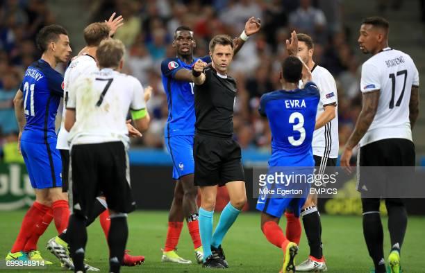Referee Nicola Rizzoli awards France a penalty for handball by Germany's Bastian Schweinsteiger