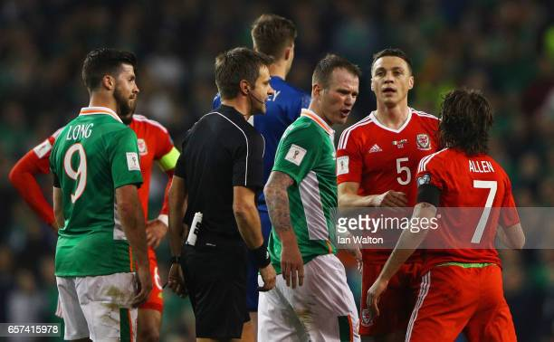 Referee Nicola Rizzoli intervenes as Glenn Whelan of the Republic of Ireland and Joe Allen of Wales clash during the FIFA 2018 World Cup Qualifier...