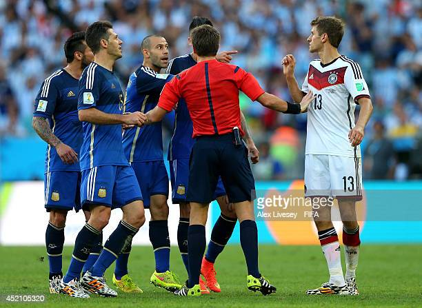 Referee Nicola Rizzoli intervenes between Thomas Mueller of Germany and Javier Mascherano of Argentina during the 2014 FIFA World Cup Brazil Final...