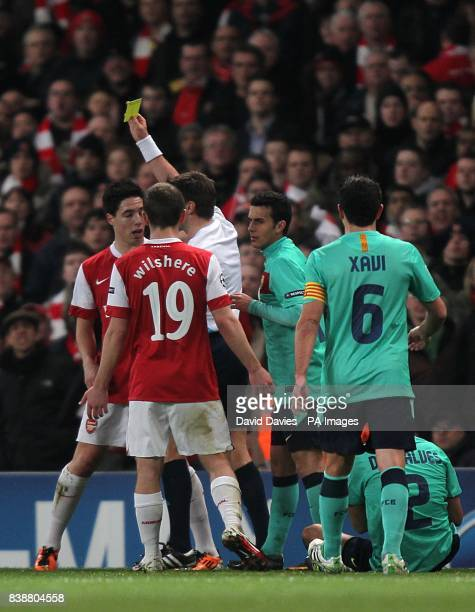 Referee Nicola Rizzoli shows the yellow card to Arsenal's Samir Nasri