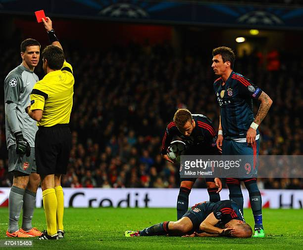 Referee Nicola Rizzoli shows Wojciech Szczesny of Arsenal a red card for a foul on Arjen Robben of Bayern Muenchen during the UEFA Champions League...