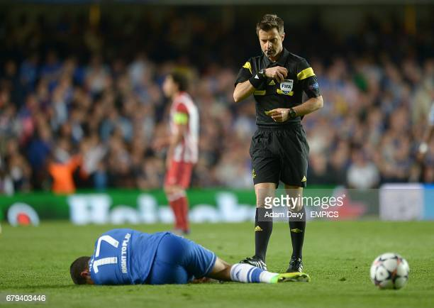 Referee Nicola Rizzoli stands over Chelsea's Eden Hazard