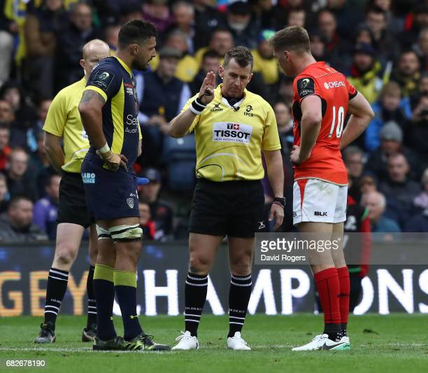 Referee Nigel Owens of Wales explains a decision to Damien Chouly of Clermont Auvergne and Owen Farrell of Saracens during the European Rugby...
