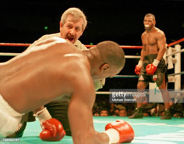 Referee Octavio Meyran counts American boxer James 'Buster' Douglas to nine as his opponent Mike Tyson looks on during the 8th round of their world...