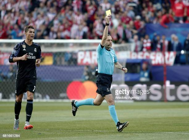 Referee of the match Cuneyt Cakir shows a yellow card during the UEFA Champions League semi final second leg match between Atletico Madrid and Real...