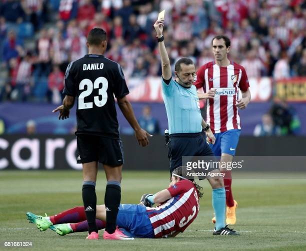 Referee of the match Cuneyt Cakir shows a yellow card to Danilo of Real Madrid during the UEFA Champions League semi final second leg match between...
