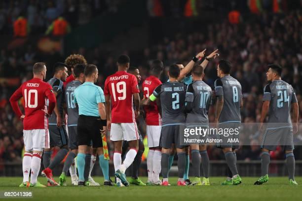 Referee Ovidiu Hategan shows a red card to Facundo Roncaglia of Celta Vigo and Eric Bailly of Manchester United during the UEFA Europa League semi...