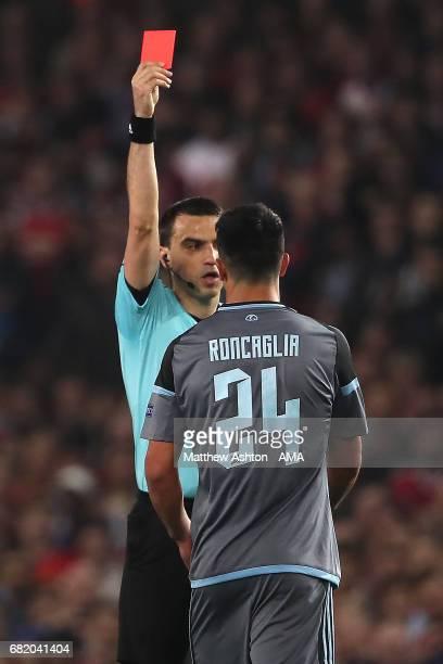 Referee Ovidiu Hategan shows a red card to Facundo Roncaglia of Celta Vigo during the UEFA Europa League semi final second leg match between...