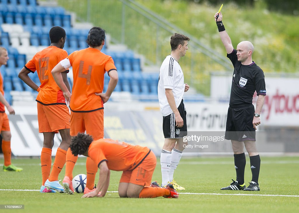 Referee Padraig Sutton shows a yellow card to Robin Yalcin of Germany during the Under 19 elite round match between U19 Netherlands and U19 Germany...