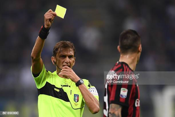 Referee Paolo Tagliavento gives a yellow card to AC Milan's defender Alessio Romagnoli during the Italian Serie A football match Inter Milan Vs AC...
