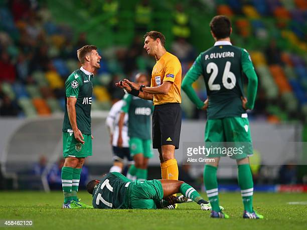 Referee Paolo Tagliavento has words with Adrien Silva of Sporting Lisbon as Nani of Sporting Lisbon lies on the pitch during the UEFA Champions...