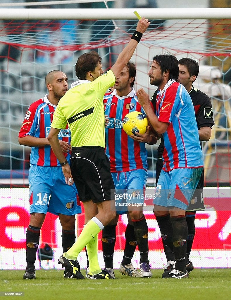 Referee Paolo Tagliavento shows a yellow card to Nicolas Spolli of Catania during the Serie A match between Catania Calcio and AC Chievo Verona at...