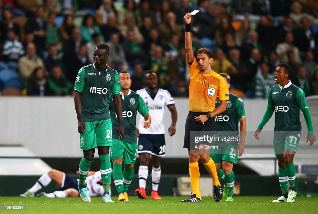 Referee Paolo Tagliavento shows <a gi-track='captionPersonalityLinkClicked' href=/galleries/search?phrase=Mouhamadou-Naby+Sarr&family=editorial&specificpeople=11332133 ng-click='$event.stopPropagation()'>Mouhamadou-Naby Sarr</a> of Sporting Lisbon a yellow card during the UEFA Champions League Group G match between Sporting Clube de Portugal and FC Schalke at Estadio Jose Alvalade 04 on November 5, 2014 in Lisbon, Portugal.