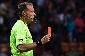 Referee Paolo Valeri gives a red card to Torino's defender Cristian Molinaro during the Serie A football match between AC Milan and Torino at San...