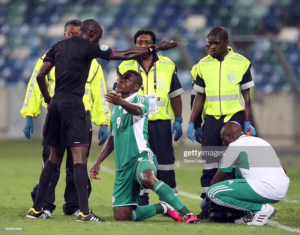 Referee Papa Backary Gassama of Gambia talks to Emmanuel Emenike of Nigeria after he stays on the floor after hurting himself during the 2013 African Cup of Nations Semi-Final match between Mali and Nigeria at Moses Mahbida Stadium on February 06, 2013 in Durban, South Africa.