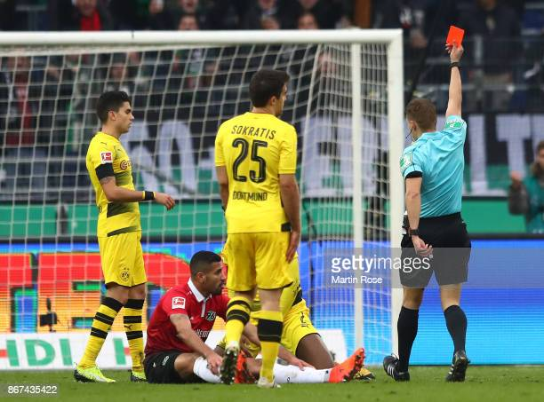 Referee Patrick Ittrich shows a red card to DanAxel Zagadou of Dortmund during the Bundesliga match between Hannover 96 and Borussia Dortmund at...