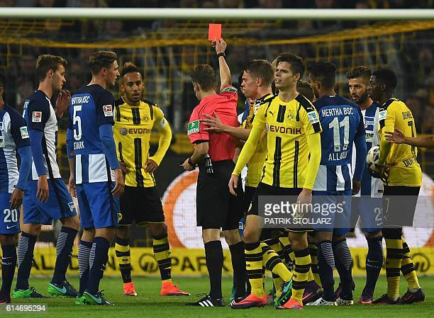 Referee Patrick Ittrich shows the red card to Dortmund's Turkish midfielder Emre Mor during the German first division Bundesliga football match...