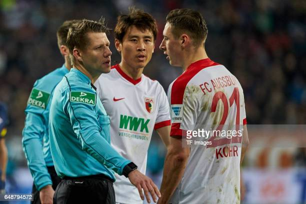 Referee Patrick Ittrich speak with JaCheol Koo of Augsburg and Dominik Kohr of Augsburg during the Bundesliga match between FC Augsburg and RB...