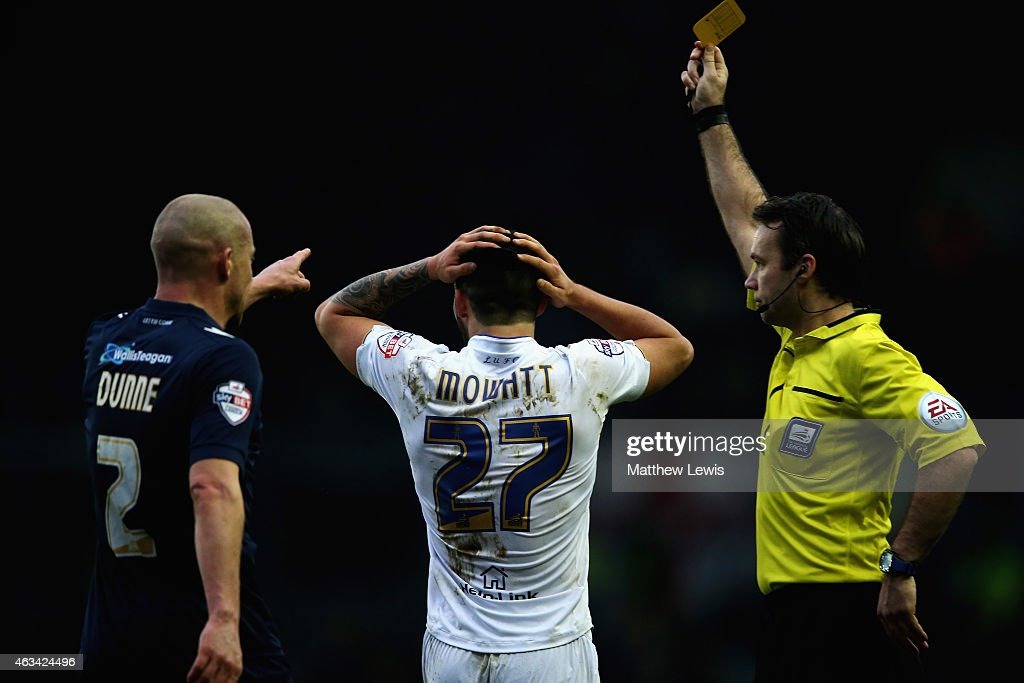 Referee Paul Tierney awards a yellow card to Alex Mowatt of Leeds United, after a challenge with Alan Dunne of Millwall during the Sky Bet Championship match between Leeds United and Millwall at Elland Road on February 14, 2015 in Leeds, England.