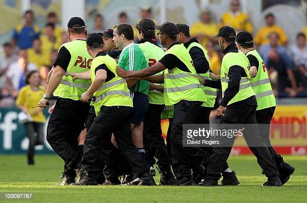 Referee Peter Allan of Scotland is surrounded by security personel as he leaves the field at the end of the Heineken Cup match between ASM Clermont...