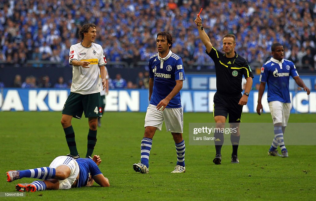 Referee Peter Gagelmann shows Roel Brouwers of Moenchengladbach the red card after a tackle against Klaas Jan Huntelaar of Schalke during the...