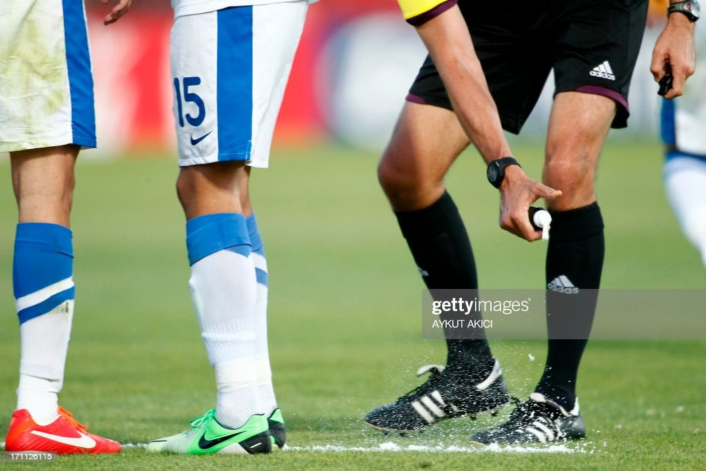 Referee Peter O'Leary from New Zealand uses vanishing spray to mark the position of the ball before a free kick during the group stage football match between Mexico and Greece at the FIFA Under 20 World Cup at the Kamil Ocak stadium in Gaziantep on June 22, 2013. AFP PHOTO/TURKPIX/Aykut AKICI