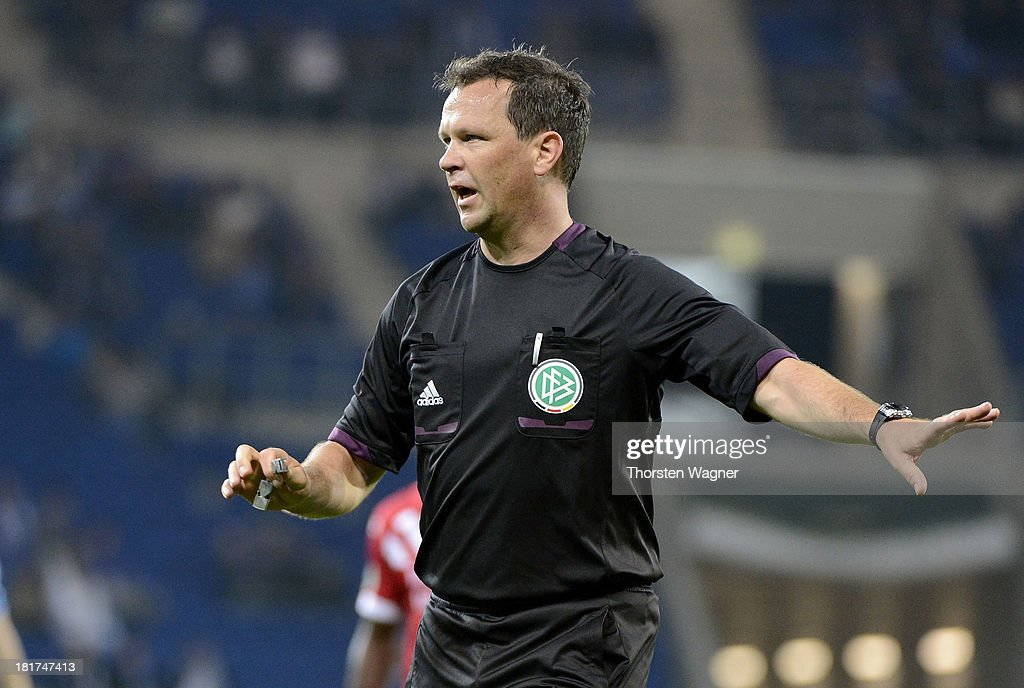 Referee Peter Sippel gestures during the DFB Cup second round match between TSG 1899 Hoffenheim and FC Energie Cottbus at Wirsol Rhein-Neckar-Arena on September 24, 2013 in Sinsheim, Germany.