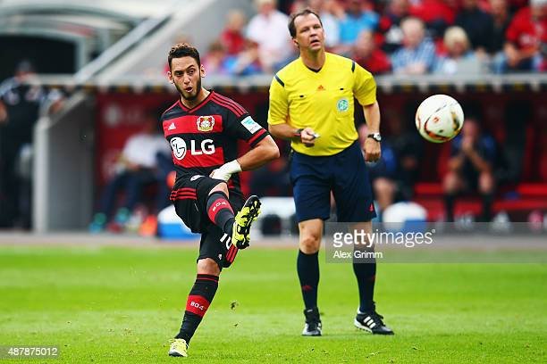Referee Peter Sippel watches Hakan Calhanoglu of Leverkusen shoot a freekick during the Bundesliga match between Bayer Leverkusen and SV Darmstadt 98...